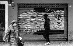 Go with the Wind (damar47) Tags: street people urban woman man art monochrome shop hair walking graffiti blackwhite store closed close wind pentax longhair citylife streetphotography monochromatic urbanart bologna oldwoman mural