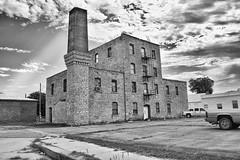 4 Storys of Stone (slammerking) Tags: bw sugarmill nationalregister historic ladder fireescpe chimney brick hutchinsonks kansas clouds sky abandoned