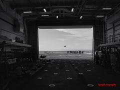 Distant Shores (Halcon122) Tags: usnavy ussjohnmurtha ship guantamobay base flightdeck flag sailors cuba bw olympusem5markii