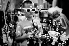 Bubble Boy (Wes Iversen) Tags: davisburg hmbt michigan monochromebokehthursday nikkor18300mm oaklandcountyfair boys bubbles carnivals fairs monochrome people shades soapbubbles sunglasses blackandwhite