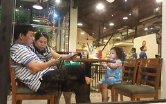 In their own worlds (Roving I) Tags: facebook smartphones parents children girls cafes nightlife concentration woodenfurniture expressions technology danang vietnam windows