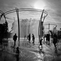 Endless Summer (tim.perdue) Tags: iphone instagram iphoneography mobile endless summer fountain bicentennial park scioto mile downtown columbus ohio city urban black white bw monochrome people figures children silhouette sunlight sun sky clouds water mist spray reflection