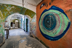 If these walls could talk (McQuaide Photography) Tags: light urban streetart art abandoned zeiss photoshop graffiti hall europe paint tallinn estonia russia availablelight decay interior painted sony tripod naturallight wideangle indoor dirty hallway urbanart prison dirt crime adobe urbanexploration walkway soviet jail inside fullframe alpha russian 16mm derelict punishment imprisonment rundown ussr cccp manfrotto lightroom penitentiary kgb urbex fsb detention wideanglelens imprisoned northerneurope correctionalfacility criminaljustice 1635mm patarei variotessar mirrorless sonyzeiss mcquaidephotography a7rii ilce7rm2