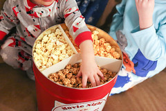 Child wearing pajamas with hand in holiday popcorn tin wth caramel, cheese and classic flavors (PersonalCreations.com) Tags: christmas boy holiday festive children kid child tub snack popcorn treat pajama
