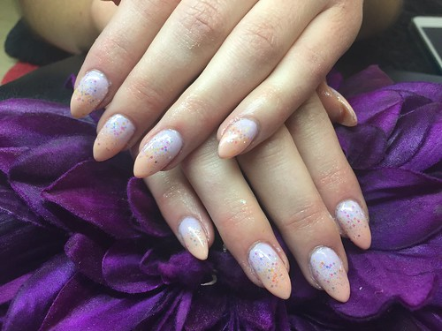 Acrylic nails with lilac and peach gel polish and glitter dust