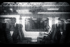 Train Solitude (marcin baran) Tags: train glass window windows layer person human sit sitting man alone lonely one sole solitude black blackwhite blackandwhite white bw monochrome mono city urban mood atmosphere rainy rain drops wated gliwice poland polaks polska marcinbaran fuji fujifilm fujix100 x100 x100t
