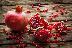 Juicy pomegranate fruit over wooden table (igorpalamarchuk) Tags: pomegranate red food wooden juicy rustic iranian ripe healthy dark table fruit sweet eating seed section drink broken pieces color iran vintage background old brown vegetarian freshness organic
