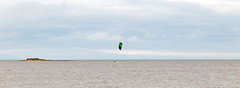one man's island (cathbooton) Tags: canonusers canoneos hilbreisland clouds water surf riverdee kitesurfing island merseyside wirral sky people sport action activity panorama wind turbines horizon lone alone sea invigorating thrilling