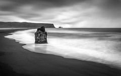 Marooned (Ffotograffiaeth Dylan Arnold Photography) Tags: sea sand waves longexposure mono blackandwhite sky clouds landscape contrast iceland dyrholaey beach volcanicbeach ocean still calm serene tranquil peaceful outdoors marooned desolate remote lonely needles cliffs stacks