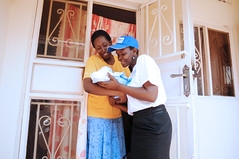 An agent greets a newborn and her mother