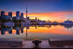 Toronto summer sunrise (kelvinsei) Tags: longexposure morning trees toronto canada building water yellow clouds sunrise logo boats woods downtown cityscape cntower mirrors lakeshore