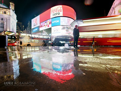 Tourist poses in the rain - Piccadilly Circus - London (Luke Agbaimoni (last rounds)) Tags: street city uk light red reflection bus london wet rain bulb night umbrella photography stream circus piccadilly piccadillycircus tubemapper