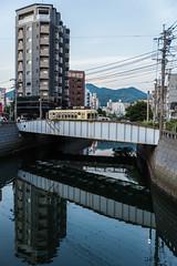 Iron bridge of trams (kmmanaka) Tags: japan nagasaki evening harbor tram dejima meganebashi scooter