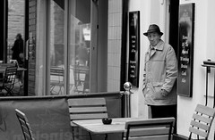 Out for a Smoke (Just Ard) Tags: street uk urban bw white man black monochrome hat wales photography prime mono pub eyecontact candid cymru cardiff streetphotography olympus smoking doorway caerdydd f18 smoker unposed 45mm omd m43 mft primelens em5 mzuiko justard justardcom