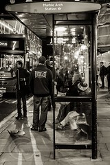 London Nov 2015 (7) 018 - Waiting for a bus on Oxford Street (Mark Schofield @ JB Schofield) Tags: park christmas street city winter england white black london monochrome canon fairground carousel hyde oxford rides nightlife wonderland stalls 5dmk3