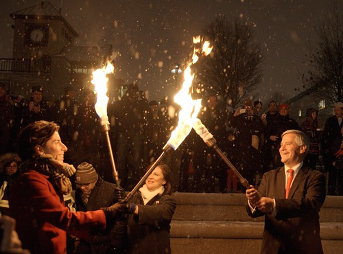 Governor Gina Raimondo passes the flame to Secretary of State Nellie Gorbea and Lt. Governor Dan Mckee during the WaterFire Lighting Ceremony. Photo by John Nickerson.