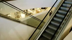 Escalators moving up and down in trade center (greycoastmedia) Tags: people man motion up modern mall person back video alone ride escalator shoppingcentre indoor down upstairs downstairs tradecenter footage movingstaircase movingstairway stockvideo greycoastmedia