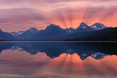 Set Ablaze (michael ryan photography) Tags: light red lake reflection water nationalpark montana glacier rays glaciernationalpark lakemcdonald crespecular michaelryanphotography sunrisebeams