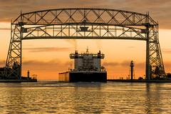 16-7432 (George Hamlin) Tags: minnesota duluth aerial lift bridge self unloading bulk carrier american integrity dawn colorful sky clouds water photo decor george hamlin photography silhouette