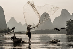 Cast Net in Black and White (lycheng99) Tags: china travel trees man motion mountains net nature birds silhouette reflections cormorants beard landscape liriver fisherman guilin curves cormorant raft shape karst guangxi bambooraft xingping cormorantfisherman castnet líjiāng karstformation