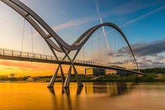 Infinity Bridge at sunset In Stockton-on-Tees, UK (Nuttawut Uttamaharad) Tags: city morning travel bridge sunset england sky moon reflection building water architecture night clouds sunrise river dark landscape foot lights march warm europe crossing purple dusk infinity united north kingdom pedestrian arches landmark illuminated east full across stockton tees stocktonontees bowstring teeside uk