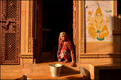 Home.  Jaisalmer (Claire Pismont) Tags: street travel woman india colour home water yellow wall ganesha bucket women colorful asia wash ganesh asie washing couleur jaisalmer rajasthan inde streetshot threshold travelphotography clairepismont