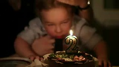 Kid's birthday. (greycoastmedia) Tags: birthday new boy party portrait people holiday motion cute home smile face childhood cake youth vintage dark dessert fun happy one video kid toddler candle child little background smoke joy young happiness blowing blow retro celebration indoors eat flame age surprise innocence present 23 years 12 anticipation wish celebrate footage caucasian lifestyles archieve stockvideo greycoastmedia
