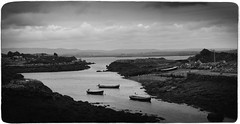 Waiting - Ireland (Firery Broome) Tags: travel ireland blackandwhite panorama seagulls seascape mountains water monochrome clouds photoshop landscape boats blackwhite europe side country olympus nik 365 fishingboats tiedup 2008 waterscape worldtravel alienskin viveza exposure7 olympus570 boatswaiting sliderssunday