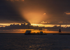 Dredging (whistlingtent) Tags: sunrise dredger sun rays crepuscular groyne north south shields ship boat seascape cloudscape golden shadows light sunlight ripples yellow orange