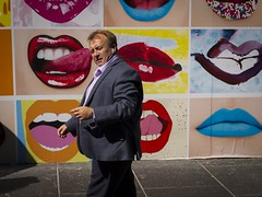 Got It Licked (Leanne Boulton) Tags: urban street candid portrait portraiture streetphotography candidstreetphotography candidportrait eyecontact candideyecontact streetlife juxtaposition humour humorous funny man male face facial expression billboard poster walking timing mouth mouths lips lick licked tongue caption colorful colouful bright laugh tone texture detail natural outdoor sunlight light shade shadow city scene human life living humanity people society culture art canon 7d 35mm color colour red blue glasgow scotland uk