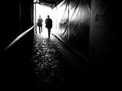 encounter (Sandy...J) Tags: olympus monochrom fotografie mono noir sonnenlicht women cobblestones kopfsteinpflaster man mann menschen frau atmosphere atmosphre blackwhite bw black bavarian bayern backlight city schwarzweis deutschland darkness dark dunkelheit durchgang einfarbig people germany gehen gegenlicht walk walking white photography passage light licht urban street streetphotography sw strasenfotografie stadt silhouette shadow sunlight strase