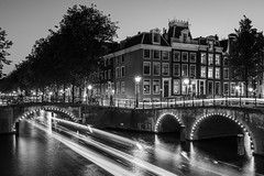 Crosstown Traffic (McQuaide Photography) Tags: amsterdam noordholland northholland netherlands nederland holland dutch europe sony a7rii ilce7rm2 alpha mirrorless 1635mm sonyzeiss zeiss variotessar fullframe mcquaidephotography lightroom adobe photoshop tripod manfrotto light licht night nacht nightphotography water reflection stad city urban waterside lowlight architecture outdoor outside waterfront gracht capitalcity capital illuminated building bridge canal keizersgracht lighttrail boat traffic speed motion movement traditional authentic classic blackandwhite blackwhite bw mono monochrome canalhouse grachtenpand longexposure