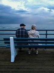 Old Love (JacobAllinson) Tags: ocean california santa old blue sky woman man love beach water bench la pier losangeles los couple pacific wind angeles santamonica gray socal monica elderly iphone