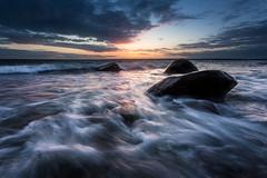 Evening Rush (Arvid Bjrkqvist) Tags: ocean sea coast water waves rocks stones blue sunset evening light horison sweden rush clouds sky