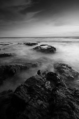 Rocks (Neuronico) Tags: ocean longexposure blackandwhite beach water monochrome rocks surf waves mood tide calm shore barnacles serene tidepools