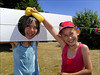 100710.049. Wet Sponge. (actionsnaps) Tags: girls friends water smiling laughing children kent sunny squeeze stocks familyfun captive fundraising margate enjoyment wethair playmates baseballcap thanet restrained charityevent summerfair pillory wetsponges northdownprimaryschool tenterdenway