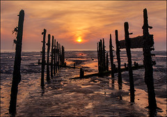Gateway to the Sunrise (adrians_art) Tags: wood old uk blue light red sea england sky orange plants white black seaweed beach water lines weather yellow clouds sunrise reflections dark gold dawn golden coast wooden kent sand waves shadows patterns tide silhouettes perspectives shore worn ripples abstracts groynes horizons leysdown verticals