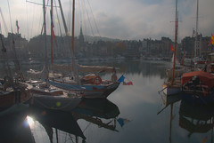 winter afternoon sun shines on yachts, reflects on water, Vieux Bassin (Old Port) Honfleur, Normandy, France (grumpybaldprof) Tags: honfleur normandy normandie france vieuxbassin oldharbour quaistecatherine quaiquarantaine quai quaistetienne stecatherine lalieutenance quarantaine water boats sails ships harbour historic old ancient monument picturesque restaurants bars town port colour lights reflection architecture buildings mooring sailing stone collombage halftimbered yachts carousel merrygoround reflections waterreflections wetreflectionsfunfair winter sun sunshine hazy haze light tamron 16300 16300mm tamron16300mmf3563diiivcpzdb016 tricolour tricoleur frenchflag marina dock