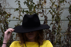 (Taran W) Tags: yellow shirt black hat shadows face people portrait portraiture hand ring green plants white wall