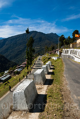 Tronsga (whitworth images) Tags: building asia street himalaya mountains himalayas rural bhutan town homes road steep white hill switchback travel trongsa people village pavement barrier trongsadzongkhag
