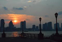 Hudson river sunset (angelsgermain) Tags: nyc newyorkcity sunset sky usa sun reflection water clouds buildings river jerseycity unitedstatesofamerica financialdistrict hudson riverfront lowermanhattan lampposts