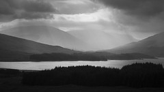 Loch Tulla (ChrisDale) Tags: trees blackandwhite cloud sun sunlight mountain lake water pine forest landscape grey mono scotland dramatic scottish hills highland shore glencoe rays loch drama beams lochtulla argyllandbute chrisdale chrismdale