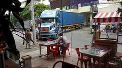 Visitor (Roving I) Tags: street stripes transport vietnam dining trucks trade awnings cafes danang logistics factories shippingcontainers plasticfurniture cabanon