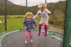 Jumping Sisters 2 (C & R Driver-Burgess) Tags: little girls kids children jumping together sisters blue top pink tights trousers vibrant multicoloured shorts blonde hair smile grin laugh wave leap farm fields paddocks green spring growth hills saddle drive fence netting obscure mask pattern play fun excitement