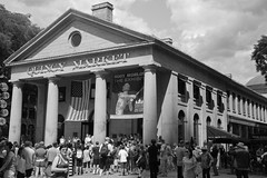 The Quincy Market (peterkelly) Tags: people bw usa building boston digital us unitedstates massachusetts unitedstatesofamerica crowd pillar americanflag northamerica column quincymarket bodyworlds starsstripes