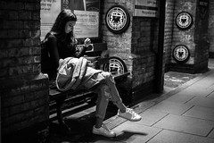 The Girl On Platform 5 (Cliff.j) Tags: girl waiting baker street underground london candid platform bench seat light brick phone station railway tube circle line hammersmith city eastbound travel sony a7 carl zeiss sonnar 55mm urban legs crossed ripped jeans trainers