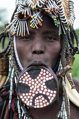 Mursi woman with clay lip plate. (Matt Wicks / GreatDistances) Tags: 2015 africa d610 eastafrica ethiopia mursi mursitribe nikkor50mmf18 nikon omo omovalley southomo clothing lippiercing lipplate piercings portrait traditionalclothing woman women