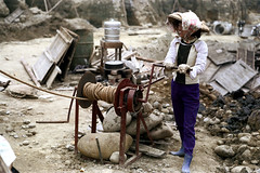 32-755 (ndpa / s. lundeen, archivist) Tags: nick dewolf nickdewolf 32 reel32 color photographbynickdewolf 1970s 1972 fall film 35mm winter republicofchina taiwan taiwanese china chinese citylife streetphotography people woman worker working construction constructionsite city crank winch hat conicalhat traditionalhat gloves boots smile smiling handcrank rope