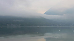 A l'aube d'un nouveau jour (Catherine Reznitchenko) Tags: france landscape annecy lake lac hautesavoie alpes water waterscape waterfront season summer daylight dawn aube aurore fog foggy mountains reflections clouds europe paysage matin morning boat barque bateau mist man homme canon calm mood atmosphere silence extrieur brume light lumire misty silhouette nature brouillard canonfrance fv10 pi