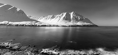 standing at the edge of land and season (lunaryuna) Tags: longexposure light bw panorama snow ice monochrome season blackwhite iceland spring le shore fjord lunaryuna mountainrange northatlantic seasonalchange northwesticeland siglufjordurlandscape